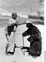 Near Lhasa. A pilgrim who measures the road with full body-length prostrations, stops to bless a woman.